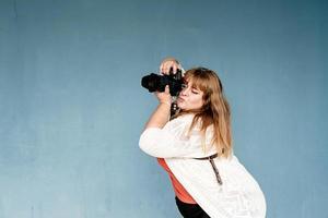 Plus-Size-Frauenfotograf im Freien auf blauem einfarbigem Hintergrund foto