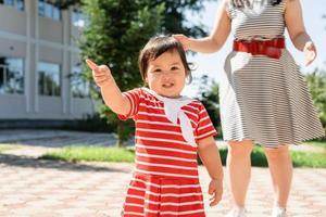 glückliche gemischtrassige Familie von Mutter und Tochter, die im Park spazieren gehen foto