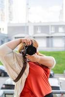 Porträt einer übergewichtigen Frau, die im Freien Bilder mit einer Kamera macht foto
