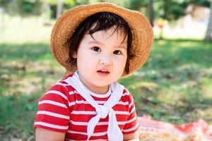 süßes kleines Baby in einem roten Kleid und Hut auf einem Picknick im Park foto