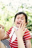 asiatisches Baby, das in Mutterhänden weint foto