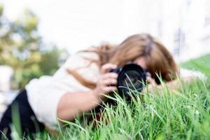 Porträt einer übergewichtigen Frau, die im Park Fotos mit einer Kamera macht