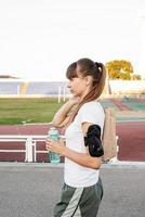 Teenager-Mädchen, das nach dem Training mit der Papiertüte im Stadion spazieren geht foto