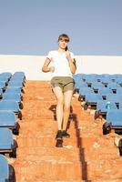 Teenager-Mädchen, das im Staduim trainiert, läuft die Treppe hinunter foto