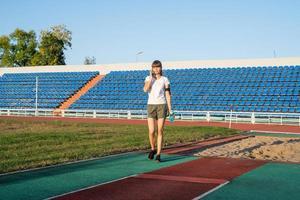 junge Sportlerin telefoniert im Stadion foto