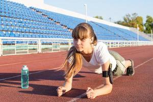 Teenager-Mädchen in einer Plankenposition beim Training im Stadion foto
