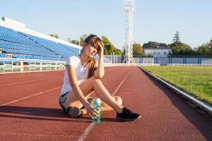 Teenager-Mädchen, das auf der Stadionbahn sitzt und sich ausruht, Trinkwasser? foto
