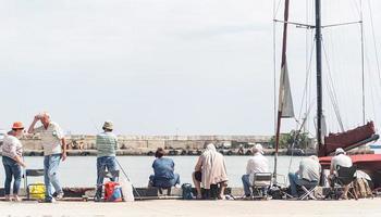 Jalta 2021 - Leute, die auf der Böschung fischen, Boote und Yachten im Hintergrund foto