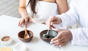 Frauenhände machen Gesichtsmaske bei Spa-Behandlungen foto