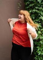 Übergewichtige Frau posiert auf der braunen festen Wand auf der Straße foto