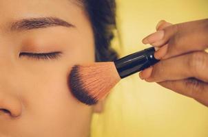Schönheitsgesicht der asiatischen Frau durch Auftragen von Bürsten auf die Haut durch Kosmetik. foto