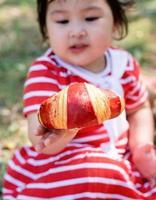 süßes kleines Baby in einem roten Kleid und Strohhut bei einem Picknick im Park foto