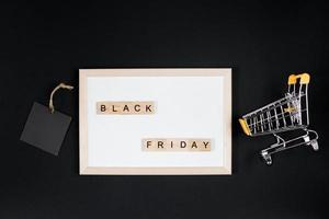 Verkauf am schwarzen Freitag. Mini-Warenkorb im Rahmen auf schwarzem Hintergrund. foto
