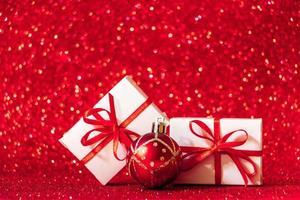 Geschenkboxen auf rotem glitzernden Hintergrund. Weihnachtskonzept foto