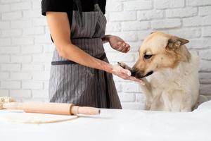 Frau, die zu Hause Teig knetet, während ihr Hund daneben sitzt foto