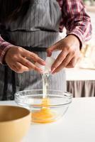 Frauenhände knacken das Ei in der Küche foto