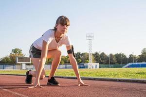 Frau auf Startposition, Vorbereitung zum Laufen auf der Stadionbahn foto