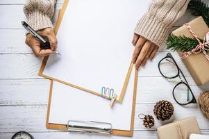 eine Hand, die einen Stift hält, um in eine Zwischenablage zu schreiben foto
