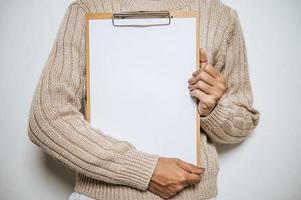 Person mit langen Ärmeln hält ein Klemmbrett auf der Brust foto
