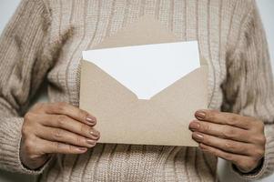 Hand hält eine offene Karte oder einen Brief und legt sie auf die Brust foto