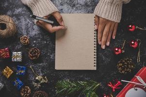 eine Hand, die einen Stift hält, um auf ein Notizbuch mit Brille zu schreiben foto