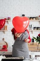 Frau in rotem Kleid und grauer Schürze mit rotem Herzballon foto