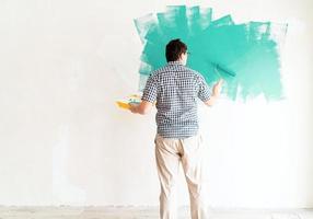 Mann färbt Wand grün mit einer Walze foto