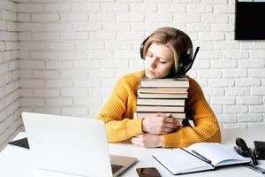 junge Frau mit schwarzen Kopfhörern, die auf einem Stapel Büchern schläft foto