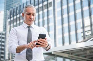 Porträt eines älteren Geschäftsmannes mit Telefon foto
