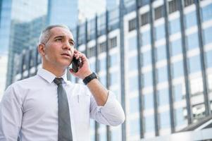 Porträt eines leitenden Geschäftsmannes, der am Telefon spricht foto