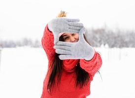 Frau, die an einem verschneiten Tag ein Rahmenschild mit ihren Händen im Freien macht foto
