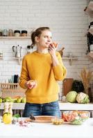 Frau riecht an einer Tomate und macht Salat in der Küche foto