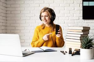 Frau, die online mit Laptop studiert, der Handy zeigt foto