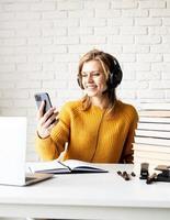 Frau studiert online mit Laptop auf der Suche nach Handy foto
