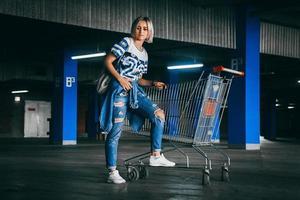 Frau in Jeans mit Einkaufswagen auf dem Parkplatz foto
