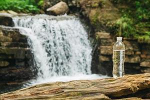 transparente Plastikflasche mit Wasser auf dem Hintergrund des Wasserfalls foto