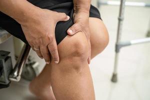 Frau mit Schmerzen am Knie foto