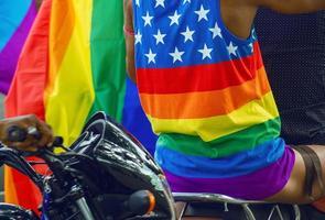 Mann trägt ein T-Shirt mit der LGBTQ-Flagge, auf der Liebesgewinne stehen. foto