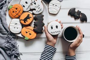Frau bereitet sich auf Halloween vor, trinkt Kaffee mit Lebkuchen foto
