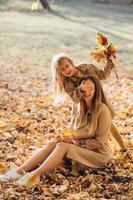 Mutter und ihre Tochter sitzen und haben Spaß im Herbstpark. foto