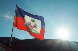 haitianische Flagge weht im Wind mit einem Sonnenuntergang, der Lichtstrahlen wirft foto