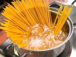 rohe Spaghetti werden in kochendem Wasser gekocht foto