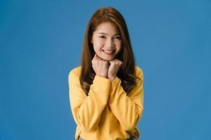 junge asiatische dame mit positivem ausdruck auf blauem hintergrund. foto