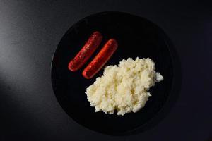gegrillte Würstchen mit Reis auf einem schwarzen Teller mit schwarzem Hintergrund foto