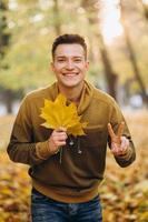 Kerl lächelt und hält einen Strauß Herbstblätter im Park foto