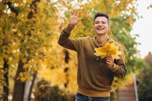 Porträt eines gutaussehenden und glücklichen Mannes, der im Herbstpark lächelt und begrüßt foto