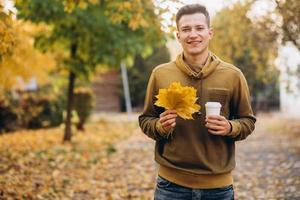 Kerl lächelt und hält einen Blumenstrauß und eine Tasse Kaffee im Park? foto