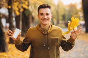 Kerl mit einem Strauß Blätter lächelt und trinkt Kaffee im Herbst foto