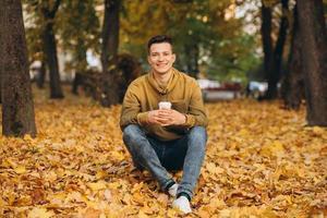 hübscher und glücklicher Junge, der im Herbstpark lächelt und Kaffee trinkt foto
