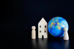 Holzhaus, Heringe und ein Globus auf schwarzem Hintergrund foto
